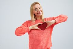 Smiley blond holding red heart. Studio shot Stock Photography
