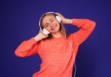 Smiley blond likes the music. Studio shot Stock Photos