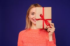 Smiley blond woman hiding face with gift box. Studio shot Stock Images