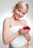 Smiley blonde with cherries in her palms Stock Photos