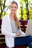Smiley blonde sitting in park with laptop Royalty Free Stock Photography