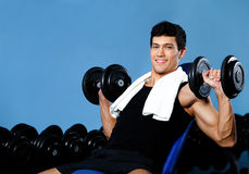 Smiley bodybuilder exercises with weights Royalty Free Stock Photos