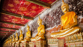 Smiley buddha statue. Has an ancient flower paintings and bricks are background,  Wat Suthat Thepwararam Bangkok Thailand, Historical place and Public place Stock Images
