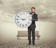 Smiley businessman holding big clock Stock Photography