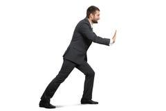 Smiley businessman pushing away something Stock Images