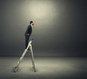 Smiley businessman on the stepladder Royalty Free Stock Photo