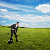 Smiley businessman vacuuming green grass Stock Photo