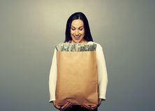 Smiley businesswoman holding paper bag. Excited smiley businesswoman holding paper bag and looking at money. photo in studio over grey background Royalty Free Stock Images
