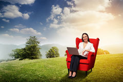 Smiley businesswoman with laptop sitting Stock Image