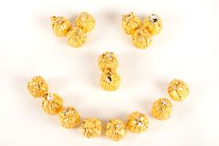 Smiley from candies. Smiley made up from chocolate candies wrapped in golden foil Royalty Free Stock Images