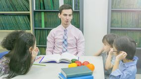 Smiley caucasian teacher and grouping of asian kids student lear Stock Photo