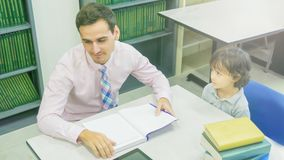 Smiley caucasian teacher and grouping of asian kids student lear Royalty Free Stock Photo