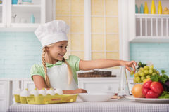 Smiley child is interested in cooking Royalty Free Stock Photo