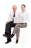 Smiley co-workers with laptop. Sitting on copyspace Stock Photo