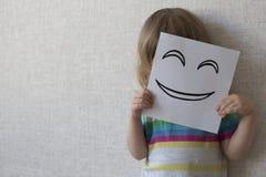 Smiley conceptual del retrato Un pequeño niño cubre su cara con una máscara divertida smiley Fotos de archivo