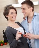 Smiley couple with goblets embraces one another Stock Photography