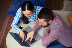 Smiley couple pointing at laptop Stock Photography