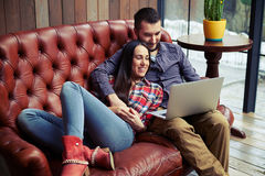 Smiley couple resting on sofa Royalty Free Stock Images