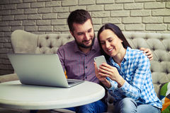 Smiley couple sitting on couch Stock Photography