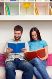 Couple sitting on sofa and reading books Royalty Free Stock Photography