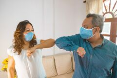 Free Smiley Couple Wearing Protective Face Masks Waving Elbows In The Workplace, Co-workers Wearing Face Covers Protect Themselves From Stock Image - 186797741
