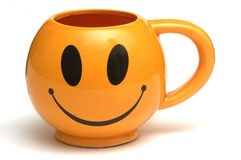Smiley cup. One orange cup with a smiling face Stock Images
