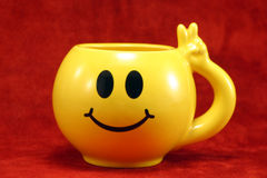 Smiley cup. Yellow Cup with smiling face on red background royalty free stock image