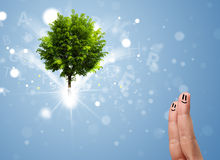smiley de doigt avec l'arbre rougeoyant magique vert Photo stock