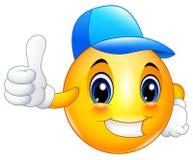 Smiley del emoticon de la historieta que lleva un casquillo y un donante pulgares para arriba Imagen de archivo libre de regalías