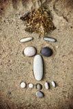 Smiley delle pietre sul primo piano della sabbia Immagini Stock
