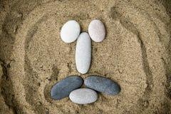 Smiley delle pietre sul primo piano della sabbia Immagine Stock Libera da Diritti