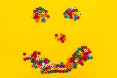 Smiley des jouets ronds multicolores sur un fond jaune images stock