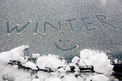 Smiley dessiné sur le pare-brise neigeux Images libres de droits