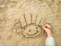 Smiley drôle sur le sable humide Photographie stock libre de droits
