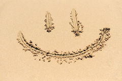 Smiley drawing on a sand Stock Image