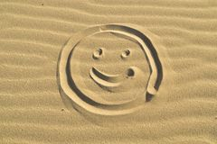 Smiley drawn in the sand. On the beach, summertime, abstract background Stock Images