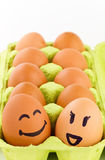 Smiley eggs. Open eggbox with smiley faces isolated on white background Royalty Free Stock Photos
