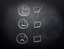 Smiley eller ledsna Checkboxes på svart tavla Arkivfoto