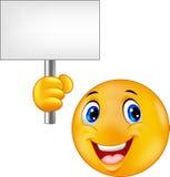 Smiley Emoticon, der ein leeres Zeichen hält Stockfotografie