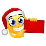 Smiley Emoticon jest ubranym Santa kapelusz podczas gdy Trzymający Czerwoną puste miejsce deskę ilustracji
