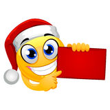 Smiley Emoticon wearing Santa Hat while Holding Red Blank Board Stock Photo