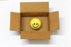 Smiley en un concepto de empaquetado de la caja de compras en línea felices fotografía de archivo libre de regalías