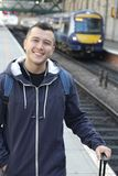 Smiley ethnic male waiting for a train.  Stock Photo
