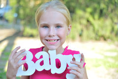 Smiley european little girl holding  wooden decoration Stock Image
