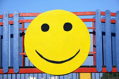 Smiley face. A wooden circular image of a smiley face hammered onto a kids playground Royalty Free Stock Photo
