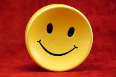 Smiley face. Yellow saucer with smiling face on red background stock photography