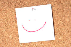 Smiley face. Pinned to a cork notice board stock photos