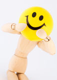 Smiley Face. Wood Model keeps Yellow Smiley Face stock photography