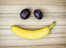 Smiley face of banana and plums, emotions, fruit theme Stock Photos