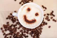 Smiley Face In Cappuccino With-Kaffeebohnen auf Tabelle Stockbild